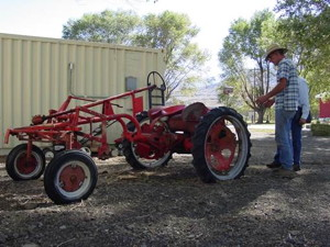 Bishop Creek Farm operator Steve Baldwin explains his newly converted electric tractor which allows him and his farming partner Bruce Willey to work more land while producing virtually no direct engine emissions.