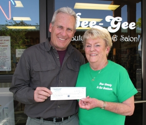 Ted Schade, ICARE President accepts donation from Becky Parham, owner of Bee Gee Beauty Supply (photo by Lisa Schade)