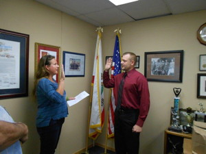 Town Clerk Jamie Gray swears in Officer Grant Zemel.
