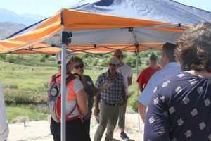 Project Manager Larry Freilich and DNR staff take advantage of shade on a summit overlooking the intake and river course.